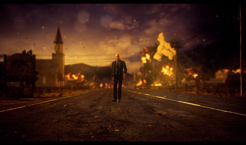 Screenshot of Agent 47 walking away like a badass, as the town in the background burns.